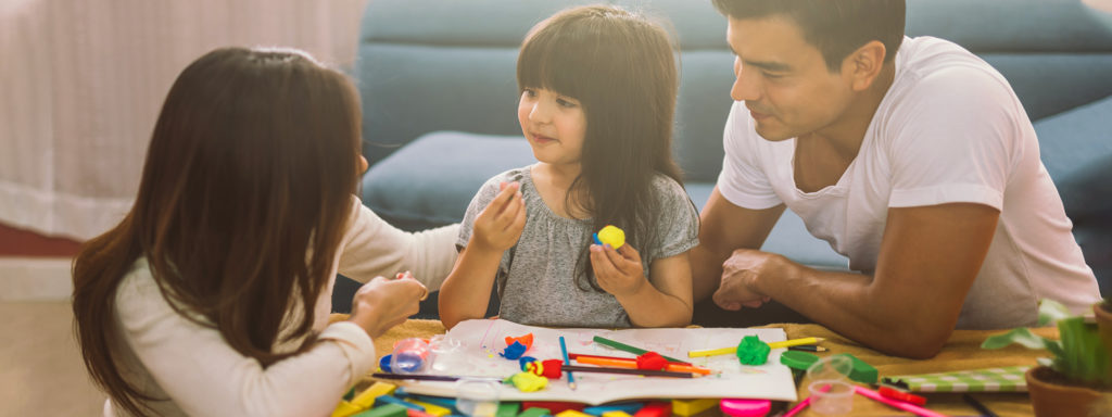 Happy family daughter girl is learning to use colorful play dough together with parents