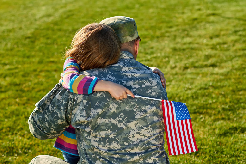 Military Service-member hugging his child good-bye before deploying.