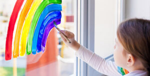 Girl painting a rainbow on window